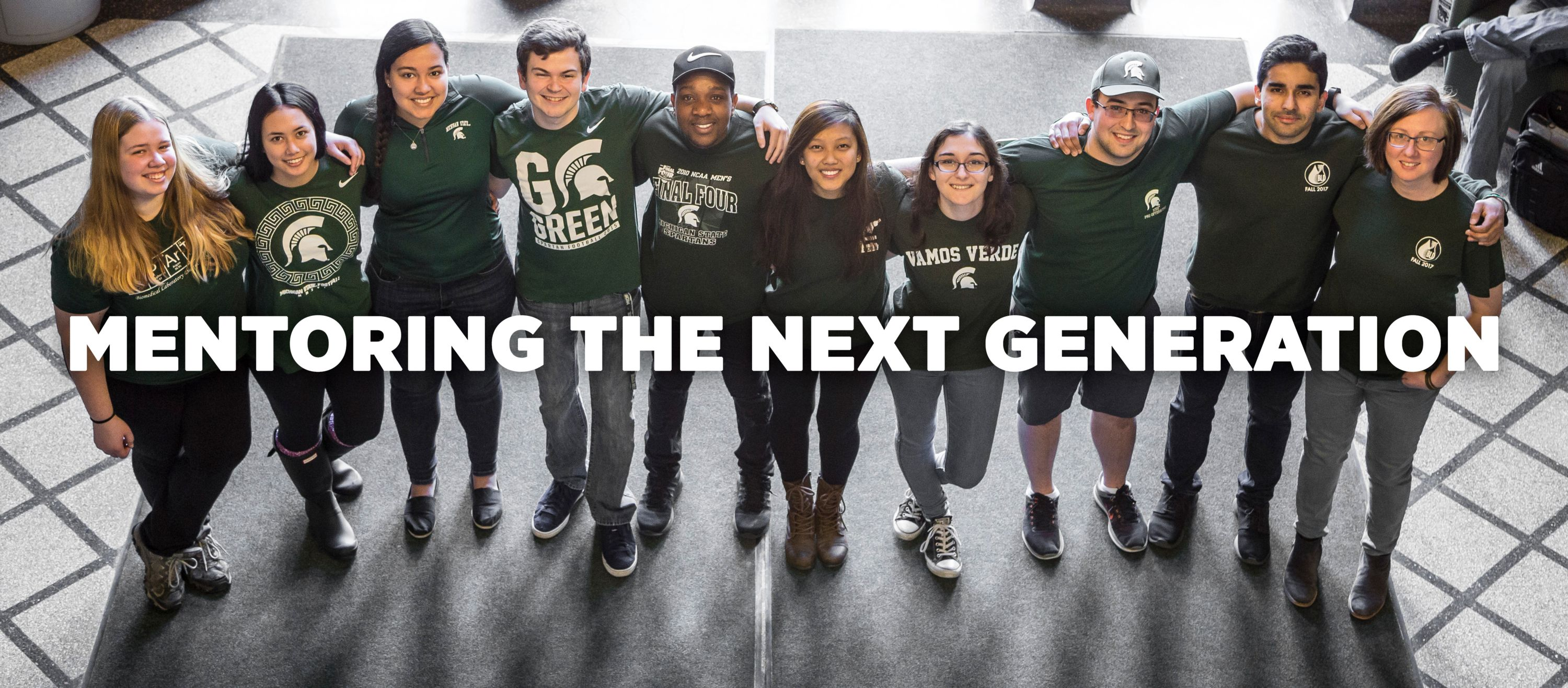 Photo of BLD students standing in the entranceway of North Kedzie Hall with the text mentoring the next generation on top of it